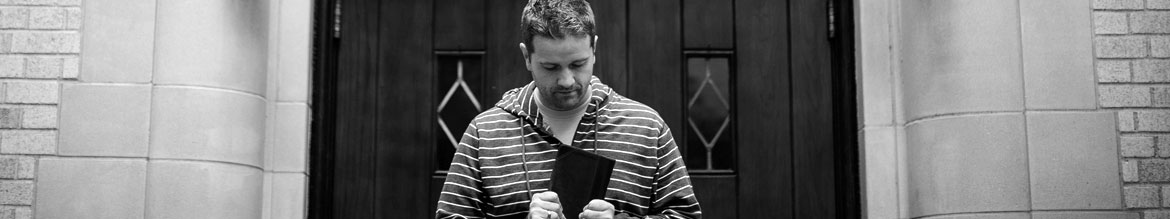 Man holding bible in front of church