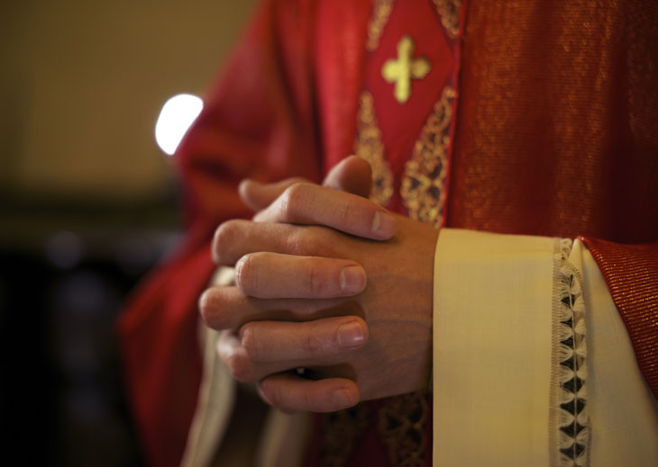 Priest with hands clasped